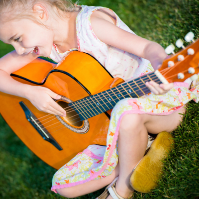 Girl playing guitar for Music lessons