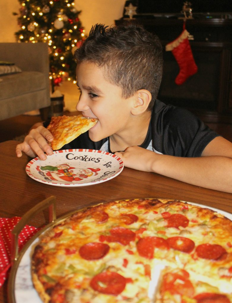 Boy Eating Pizza near Christmas Tree